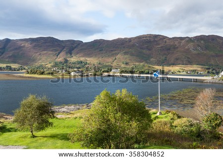 Scottish flag waving in the wind near Eilean Donan castle in Dornie, between Skye and the Highlands of Scotland. The sunny light baths the lush greenery and the bridge linking the road over the loch. - stock photo