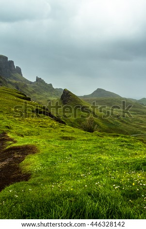 Scottish landscape at the Quiraing, Isle of Skye with a saturated, vibrant and lush green grass meadow and hills and mountain peaks and a cloudy overcast sky - stock photo