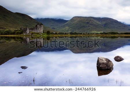 Scottish landscape with a ruined castle is reflecting in the loch  - stock photo