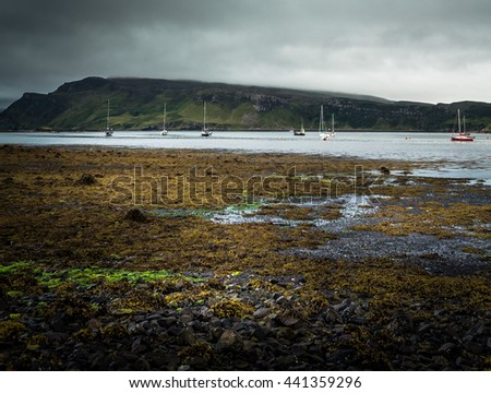 Scottish Seascape On Beach With Sailboats And Hill In Background With Stormy Cloudy Sky - stock photo