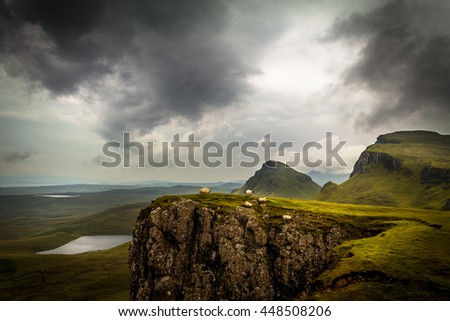 Scottish sheep on the ledge of a cliff on the Quiraing, Isle of Skye, Scotland, UK with lush, saturated green grass, dramatic clouds and valley as well as hill and mountain peaks in background - stock photo