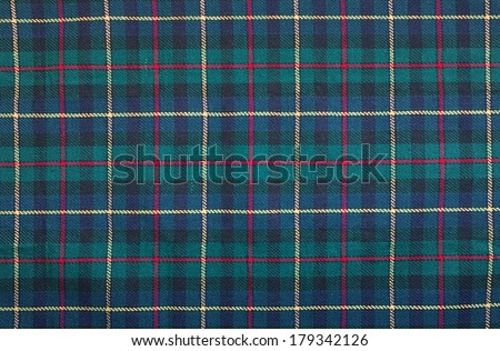 Scottish tartan background a checked plaid weave pattern with red, green blue and yellow colours. - stock photo