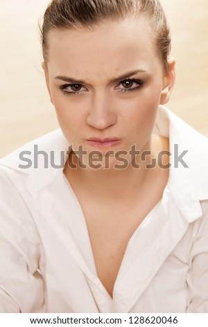 Scowling pretty girl posing in white shirt - stock photo