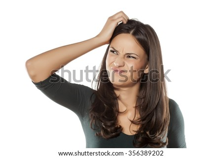 scowling young woman scratching her head - stock photo