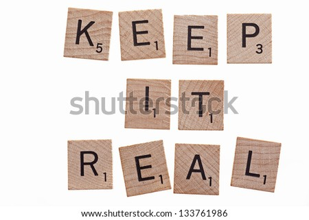 scrabble letters spelling keep it real on white background - stock photo