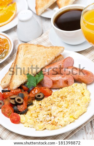 scramble eggs with tomatoes, grilled sausages and toast, vertical, top view