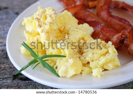 Scrambled eggs and bacon with a sprig of Rosemary. - stock photo