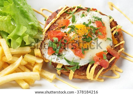 Scrambled eggs on burgers with fries and salad - stock photo
