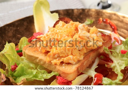 Scrambled eggs on toast and fresh salad