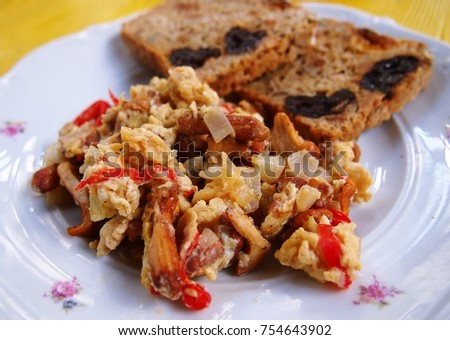 Scrambled Eggs With Chanterelle Mushrooms Onion And Tomatoes Served Toasted Whole Grains Bread Mixed