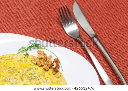Scrambled eggs with dill and walnuts. Close up view, focus on dish - stock photo