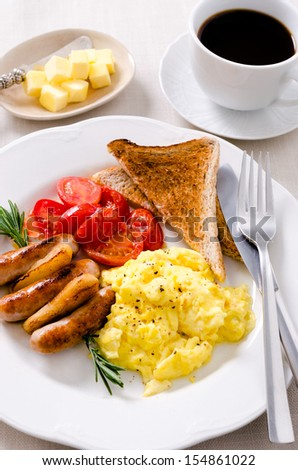 Scrambled eggs with fried tomatoes, pork sausages chipolata and wholemeal toast, full breakfast served with coffee - stock photo