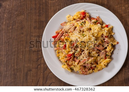scrambled eggs with ham, vegetables and cheese in a plate on wooden table