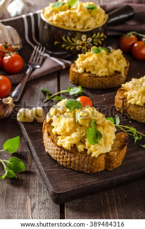 Scrambled eggs with herbs and garlic on toasted bread, delicious and fresh herbs