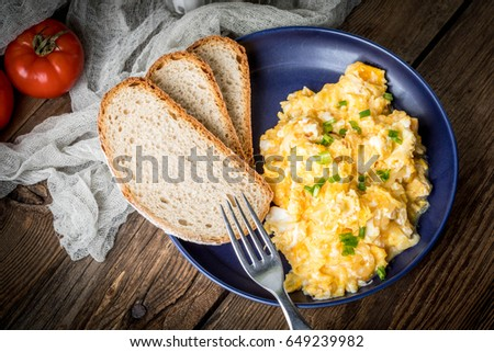 Scrambled Eggs With Onion And Chives Served With Bread On A Blue Plate Top View