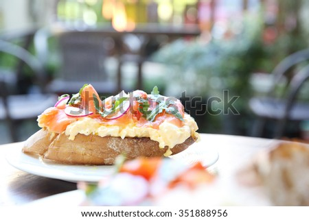Scrambled eggs with smoked salmon and whole wheat toast  - stock photo