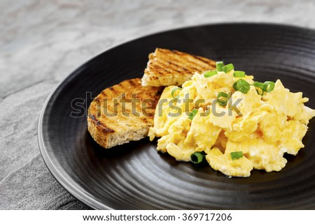Scrambled eggs with toast on black plate. - stock photo