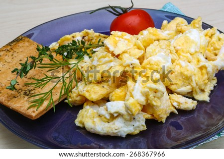 Scrambled eggs with tomato, dill and black olive - stock photo