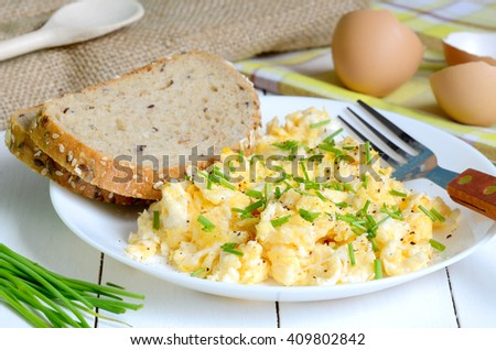 Scrambled eggs with wholemeal bread and fresh chives on white wooden table. Fried eggs on white plate with bread. - stock photo