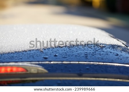 scraping snow and ice from the car roof - stock photo