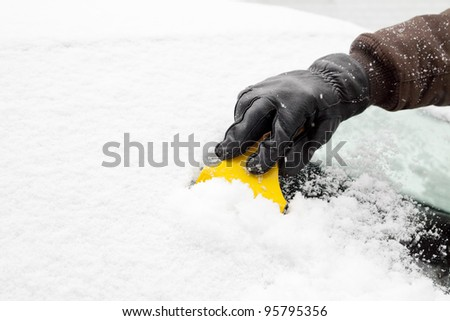Scraping snow and ice from the car windscreen - stock photo