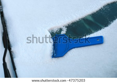 scraping snow and ice from the car windshield... - stock photo