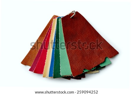 Scraps of colored leather fastened a metal clip on a white background - stock photo