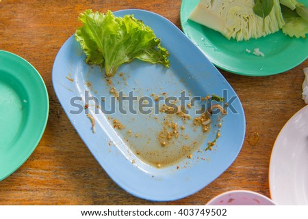 Scraps of food left in plastic dish on table. - stock photo