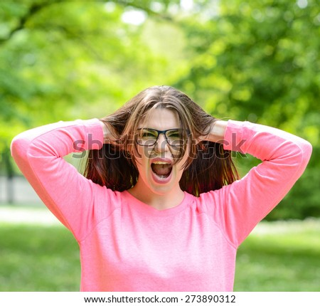 Scream - Beautiful young woman screaming and pulling hair outdoors - stock photo