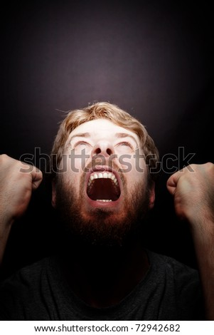 Scream of rebellion - angry furious man in the dark - stock photo