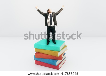 Screaming businessman with hands up high standing on colorful book stack on light background. 3D Rendering - stock photo