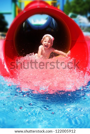 Screaming girl riding down the water slide - stock photo