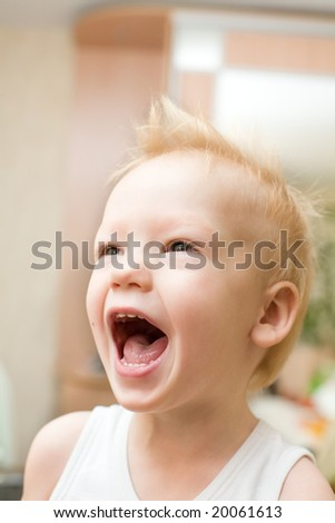 Screaming happy boy with funny hairstyle at home - stock photo