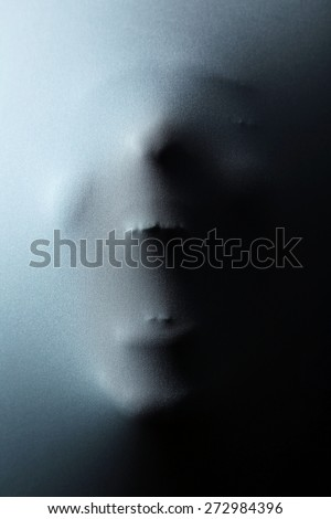 Screaming human face pressing through fabric as horror background