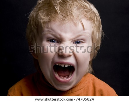 Screaming little blond  boy on black background