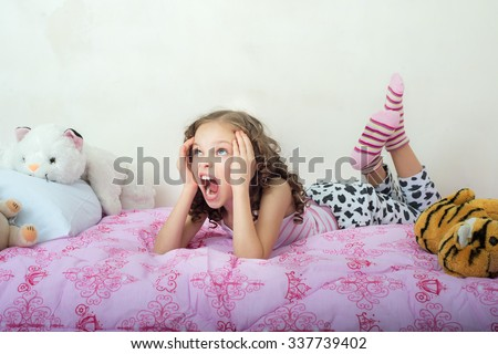 Screaming little girl lying on her bed. Facial expression, Emotions. - stock photo