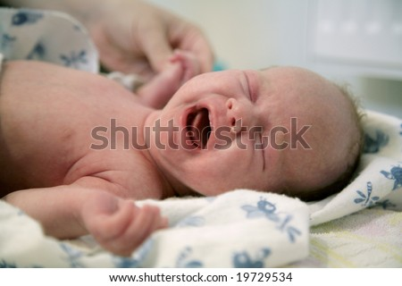 Screaming newborn baby on changing table - stock photo