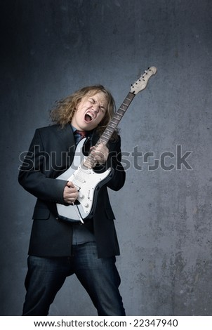 Screaming rock superstar with electric guitar - stock photo