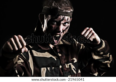 screaming soldier want's to fight with enemy. studio shot over black background