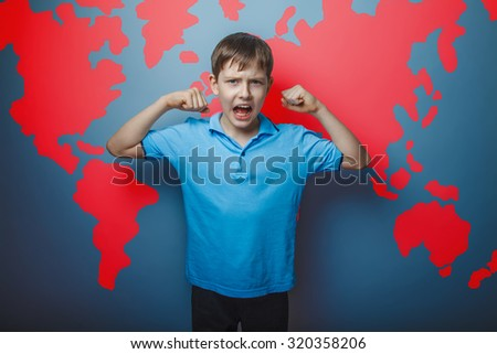 screaming teenage boy shows the strength of the biceps raised his arms on the background of a world map infographics
