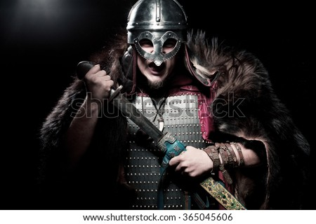 Screaming viking warrior with sword, armour and helmet over black background - stock photo
