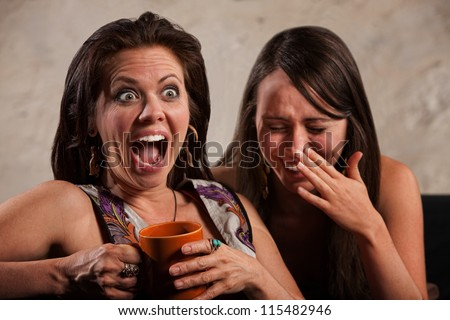 Screaming woman holding coffee mug next to laughing friend - stock photo
