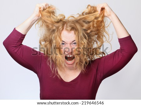 Screaming Young Woman Pulling Out Hair. - stock photo