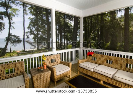 screen porch with beach view and wicker furniture - stock photo
