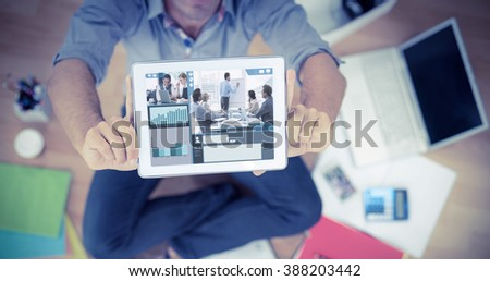 Screen with graphs against businessman showing tablet computer in creative office - stock photo