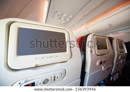 Screens for passengers in back of soft seats in modern airplane. - stock photo