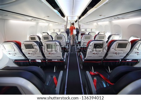 Screens in back of soft seats and back of passenger in modern airplane. - stock photo