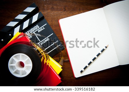 Screenwriter desktop detail with clapper, film reel notebook and pencil - stock photo
