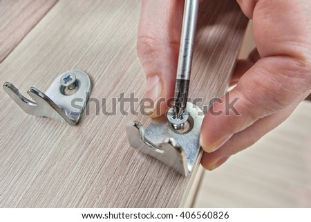 Screw Being Screwed In Wooden Furniture using phillips screwdriver close-up.  - stock photo