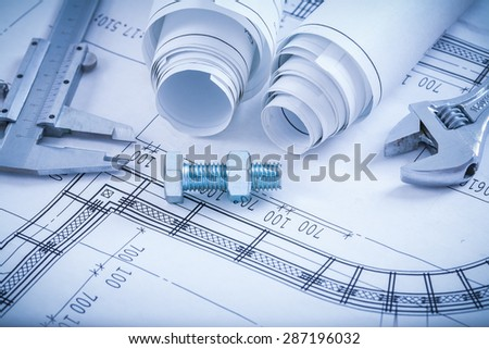 Screw bolt with nut adjustable key slide caliper rolls of construction plans on blueprint architecture and building concept. - stock photo